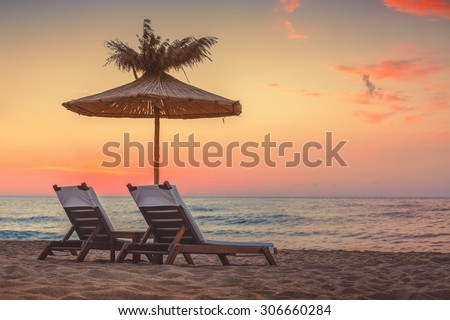 Vivid sunrise on a beautiful sandy beach with sunshade  #306660284
