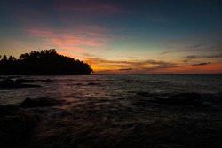 Vivid sunset sky waterscape and silhouette forest island background