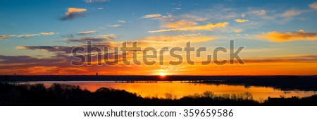 Vivid Texas sunrise over Benbrook Lake with colorful reflections on the water