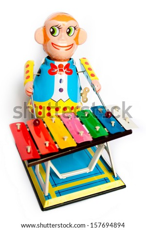 vivid tin toy  wind up monkey musician retouched and isolated on white background