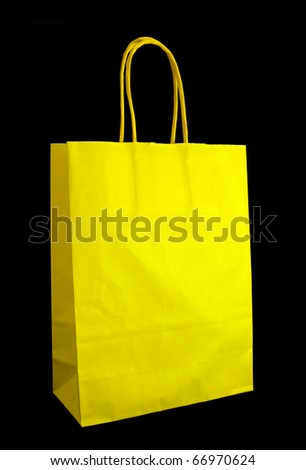 Vivid yellow paper carrier bag / shopper isolated over black