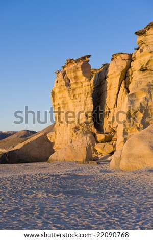 Vividly colored cliffs sharply edged against a bright blue sky in the early morning sun.