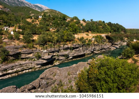 Vjosa river in South Albania embedded in interesting rock landscape with bridge and mountains in the background, Permet district, Albania