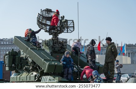 VLADIVOSTOK, RUSSIA - FEBRUARY 23, 2015: Children play on modern russian armored vehicle during festivities devoted to Defender of the Fatherland Day.