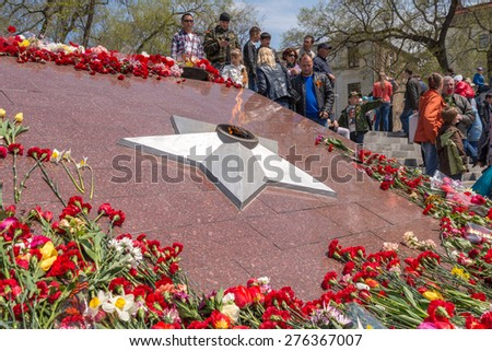 VLADIVOSTOK, RUSSIA - MAY 9, 2015: Eternal fire surrounded by flowers on May 9th in day of Victory.