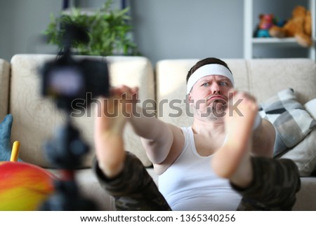Vlogger freak shows his subscribers on camera how not to do the stretching correctly, holding his hands over his feet. Astonished face expression grimaces aganist home background concept