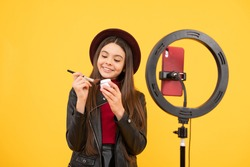 vlogger with powder brush. making video blog on phone. blogging ring lamp. weblog and vlog. makeup tutorial. influencer. happy teen girl use selfie led. kid beauty blogger. cheerful child do makeup.