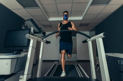 VO2 max test. Fit young man running fast on treadmill with a mask. Athlete examining his performance in sports science lab.