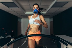 VO2 max test. Sportswoman with mask running on treadmill. Female athlete in sports science lab measuring her VO2 max.