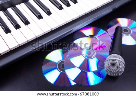 Vocal microphone,cd discs and electronic keyboard. Closeup on black table