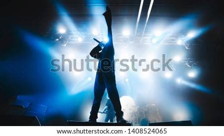vocalist performing on stage at a concert in the fog. Dark background, smoke, concert  spotlights. #1408524065