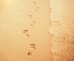 Vocation concept. Foot steps on the sand. Copy space.