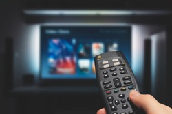 VOD service on television. Man watching TV, streaming service, video on demand, remote control in hand.