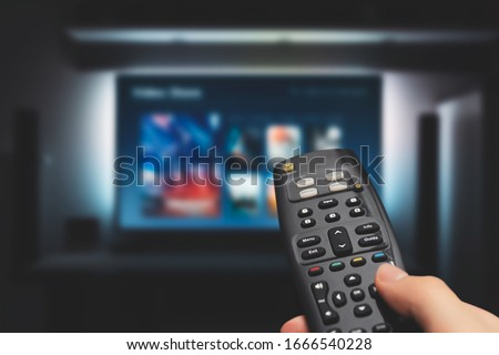Photo of  VOD service on television. Man watching TV, streaming service, video on demand, remote control in hand.