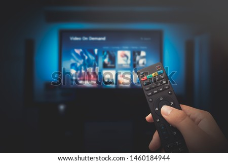 Photo of  VOD service screen. Man watching TV with remote control in hand.