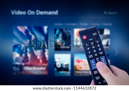 VOD service screen with remote control in hand. Video On Demand television internet stream multimedia concept #1144632872