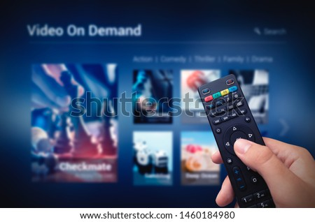 VOD service screen with remote control in hand. Video On Demand television internet stream multimedia concept #1460184980