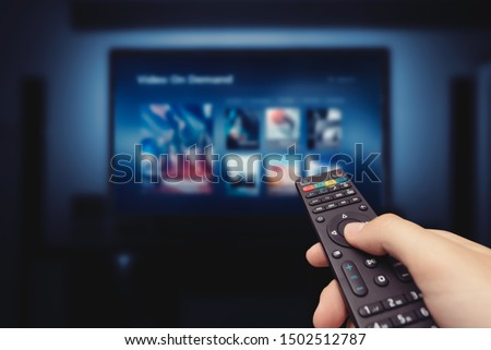 Photo of  VOD service screen with remote control in hand. Video On Demand television internet stream multimedia concept
