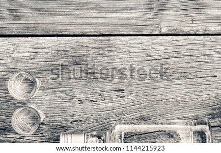 Vodka in a bottle on a wooden background. Concept: Vodka Luxury Alcohol. Copy space