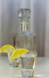 vodka in a glass with lemon on a white background