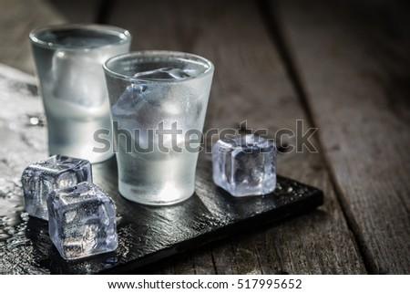 Vodka in shot glasses on rustic wood background Zdjęcia stock ©