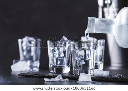Vodka in shot glasses pouring out of the bottle on black stone background, iced strong drink in misted glass Zdjęcia stock ©