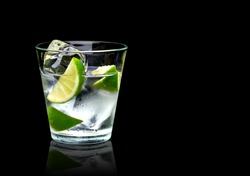 Vodka lime mojito or gin tonic  with ice in rocks glass on black background including clipping path