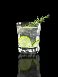 Vodka, lime wedge with ice in rocks glass on black background with reflection