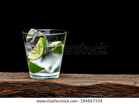 Vodka, lime wedge with ice in rocks glass on log with black background