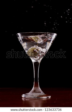 vodka martini isolated on a black background with an olive splashing and air bubbles