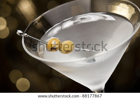 Vodka Martini with olive garnish in front of a gold glitter background