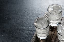 Vodka on the rocks on an old wooden table as detailed close-up shot closeup