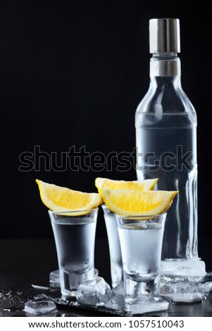 Vodka. Shots, glasses and bottle with vodka and lemon with ice .Dark stone background.Copy space .Selective focus #1057510043