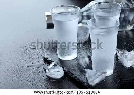 Vodka. Shots, glasses with vodka with ice .Dark stone background.Copy space .Selective focus Zdjęcia stock ©