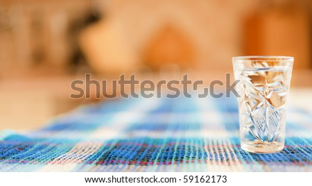 Vodka wine-glass on table covered with blue cloth.