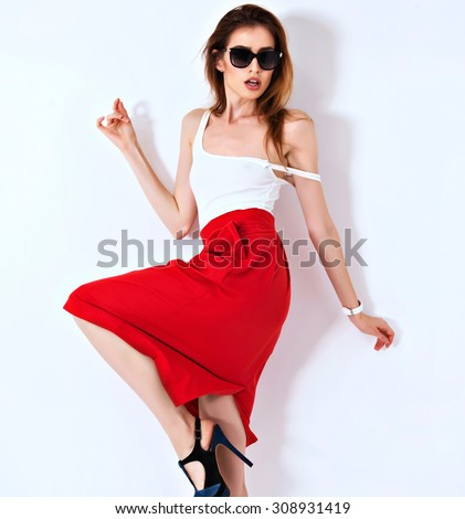 Vogue fashion model woman posing in red mini skirt on white studio background