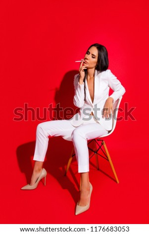 Stock Photo Vogue photoshooting studi concept. Portrait of slim skinny woman smoking cigarette wearing white suit sitting on chair isolated on vivid red background