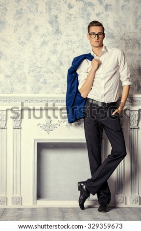 Vogue shot of a handsome elegant man in a suit posing in vintage interior. Men\'s beauty, fashion.
