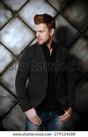 Vogue shot of a handsome man in black suit posing at studio. Men\'s beauty, fashion.
