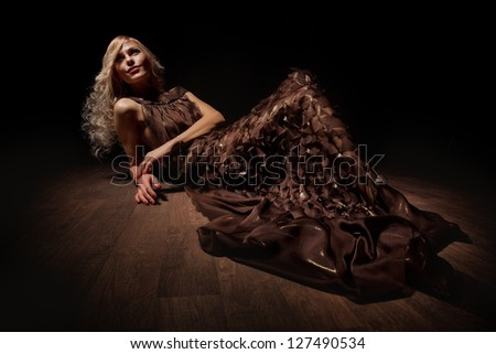 Vogue style photo of a young Blonde in brown dress