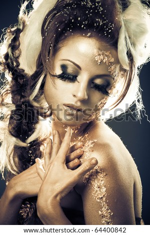 Vogue style portrait of a woman with gold-silver bodyart and makeup
