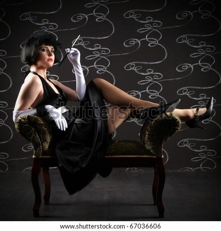 Vogue style vintage portrait. Retro-stylized smoking woman with mouthpiece sitting on black sofa.