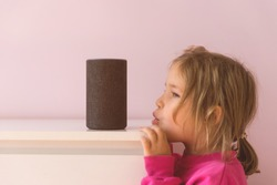 voice controlled smart speaker. Little kid girl talking to talking to Amazon Alexa Echo Dot. Education programme for child. kid girl talking to Alexa and give it orders and commands what to switch on.