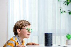 Voice controlled smart speaker. Little kid girl talking to talking to Amazon Alexa Echo Dot. Education programme for child. Boy talking to Alexa and give it orders and commands what to switch on