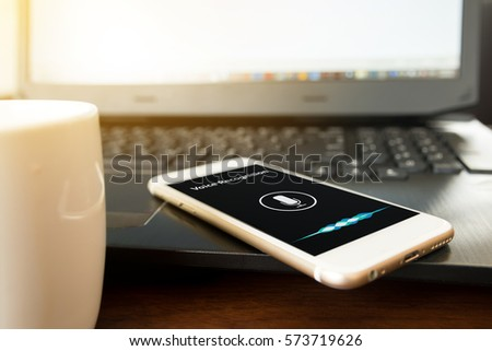 Voice recognition , speech detect and deep learning concept. Application on mobile phone screen in coffee shop background with flare light effect #573719626