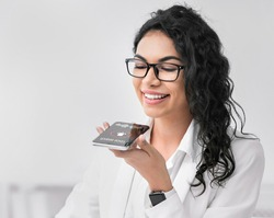 Voice Search. Mexican Businesswoman Using Smartphone Personal Help Service App Browsing Internet Sitting At Workplace Indoor