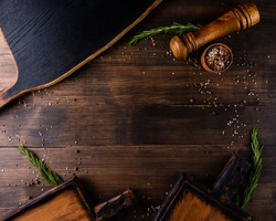 Void wooden background and cutting board with wooden texture and scattered spices on it. wooden cutting boards on a brown table with space for copy space.