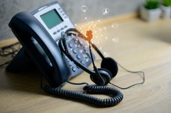 VOIP services concept of IP telephone device and headset with flying icon of voip services