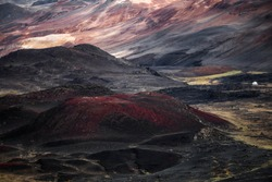 Volcanic landscapes of northeastern Iceland, surrounding Krafla volcano with a small building from the local geothermal power plant in the distance and various shades of color caused by volcanic rock