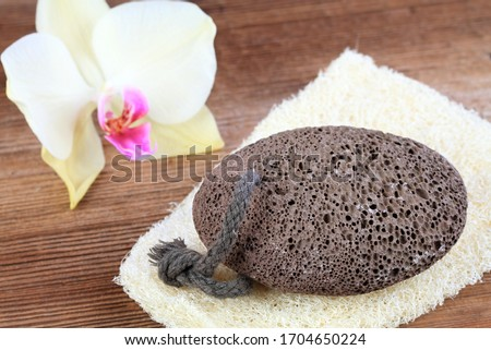 Volcanic pumice stone on the  washcloth  in rustic style. Pumice stone with a string on the wooden table, decorated with beautiful orchid.   Stockfoto ©
